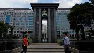 People walks near the fountain of Indonesia's central bank, Bank Indonesia, in Jakarta